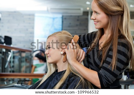 Side view of hairdresser combing hair of female customer before haircut - stock photo