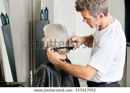 Side view of hairdresser examining hair length of female client at salon - stock photo