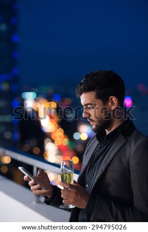 Side view of handsome man with a glass of champagne using smartphone - stock photo