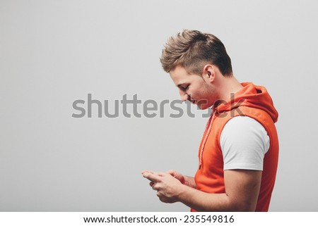Side view of handsome young man in white shirt with red jacket, busy using his cellphone with copy space on left side. Isolated on Light Gray.