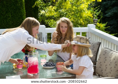 Side view of happy mother putting hat on younger daughter while eating breakfast outdoors, during summer time, on patio with woods in background  - stock photo