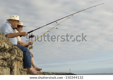 Side view of happy senior couple fishing against cloudy sky - stock photo