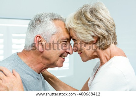 Side view of happy senior couple standing face to face in bedroom at home