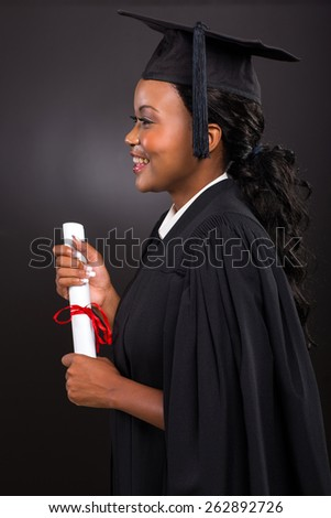 side view of happy young african female graduate on black background - stock photo