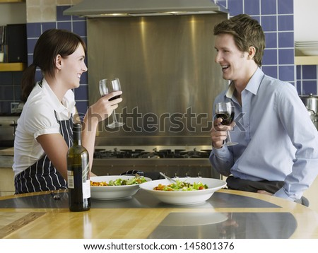 Side view of happy young couple drinking wine in kitchen - stock photo