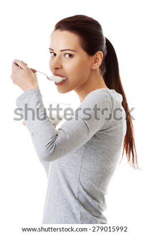 Side view of healthy woman eating natural yoghurt. - stock photo
