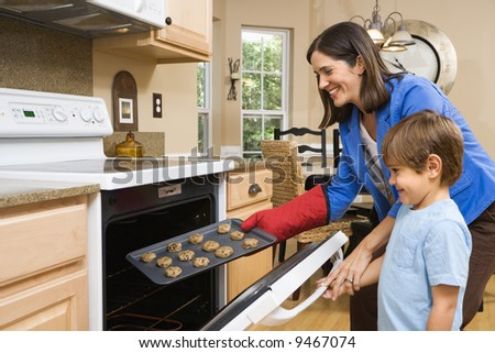 Side view of Hispanic mother and son putting cookies into oven. - stock photo