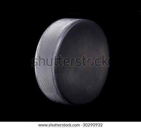 side-view of hockey puck on black background