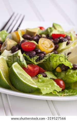 Side view of homemade southwest black bean lime salad with corn, cherry tomatoes, lettuce, avocado, and black beans with vinaigrette dressing for clean eating - stock photo