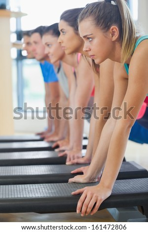 Side view of instructor with fitness class performing step aerobics exercise in gym - stock photo