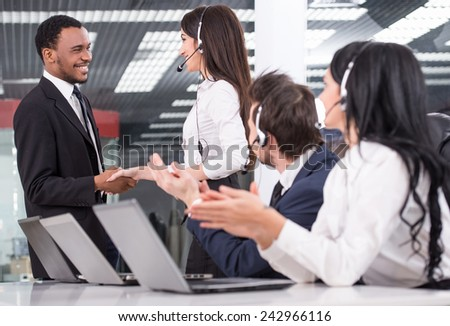 Side view of line of call centre employees are smiling and working on computers. Two of them are shaking hands. - stock photo
