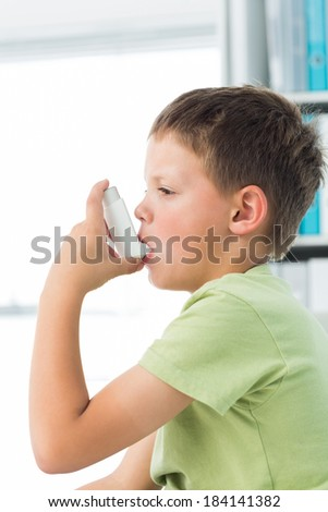 Side view of little boy using asthma inhaler in hospital - stock photo