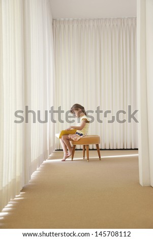 Side view of little girl reading book on stool in corner of room - stock photo