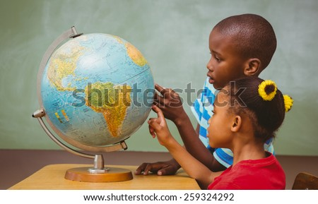 Side view of little kids pointing at globe in classroom - stock photo