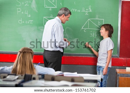 Side view of little schoolboy asking question to teacher while solving mathematics on board in classroom - stock photo