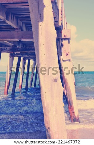 Side view of long jetty pier overlooking sandy beach with retro vintage filter. Vertical. - stock photo