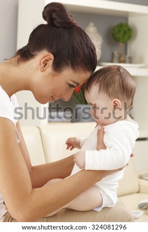 Side view of loving mother and little boy at home. Forehead together. - stock photo