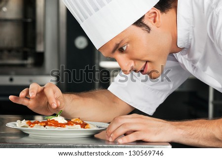 Side view of male chef garnishing dish at kitchen counter - stock photo