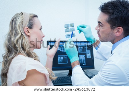 Side view of male dentist showing woman her mouth x-ray - stock photo
