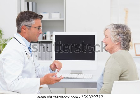 Side view of male doctor conversing with senior patient at table in clinic - stock photo