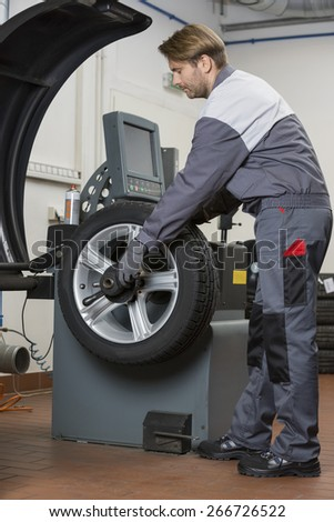 Side view of male mechanic repairing car's wheel in workshop - stock photo