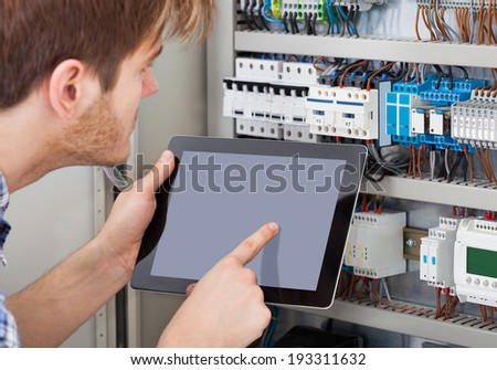 Side view of male technician examining fusebox while holding tablet