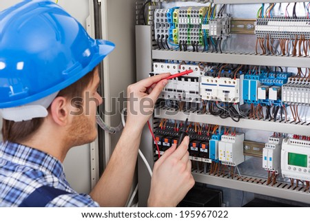 Side view of male technician examining fusebox with multimeter probe - stock photo