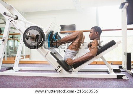 Side view of male weightlifter doing leg presses in gym - stock photo