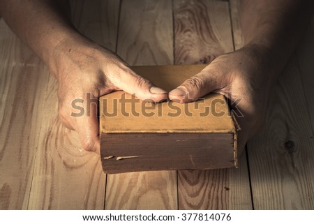 side view of man holding the bible in the darkness over wooden table.vintage effected photo. - stock photo