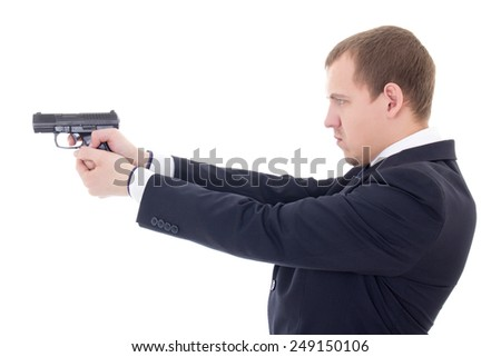 side view of man in business suit shooting with gun isolated on white background - stock photo