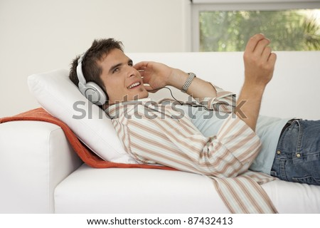 Side view of man laying down on a white sofa listening to music at home.