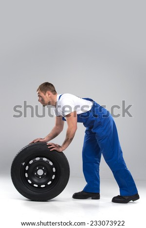 side view of man rolling tire on grey background. studio shut of dirty guy looking ahead - stock photo