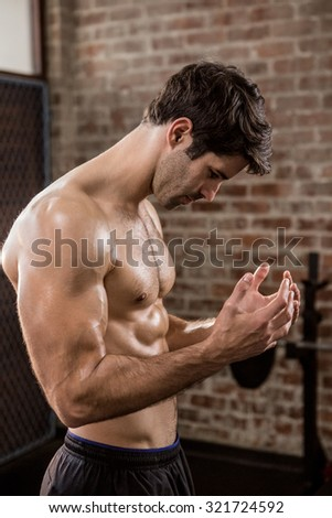 Side view of man showing his body at the gym - stock photo