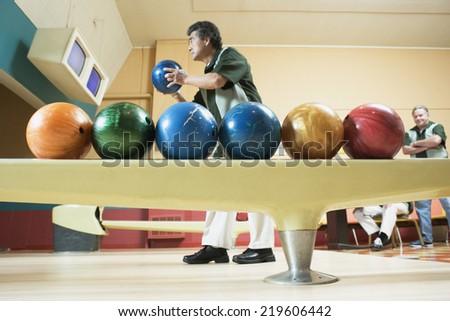 Side view of man with bowling balls - stock photo
