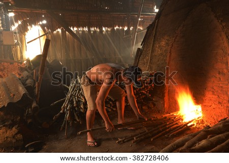 Side view of man worker work on a pile of slow burning wood in Charcoal factory .mangrove wood has been processed as charcoal from a cone in Bangtaboon Petchaburi Thailand - stock photo
