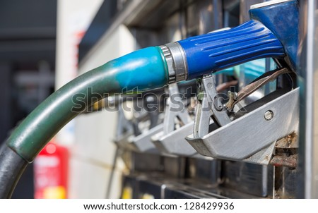 side view of many gas pump nozzles with shallow depth of field - stock photo