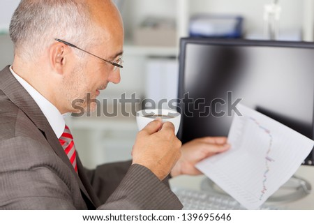Side view of mature businessman analyzing line graph while holding coffee cup in office - stock photo