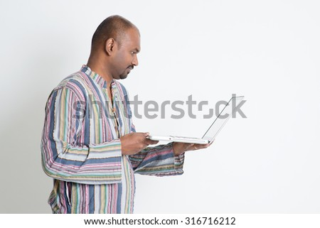 Side view of mature casual business Indian man using laptop computer, looking at pc screen, standing on plain background with shadow.