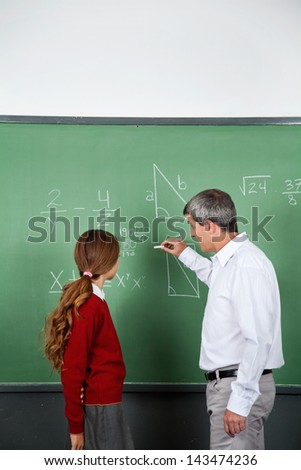Side view of mature male teacher teaching mathematics to teenage girl in classroom - stock photo
