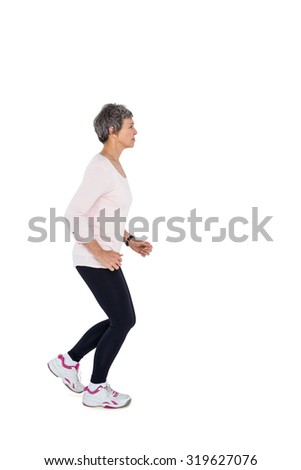 Side view of mature woman jogging against white background - stock photo