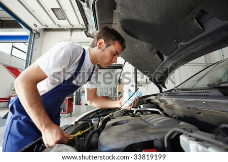 side view of mechanic checking motor oil - stock photo