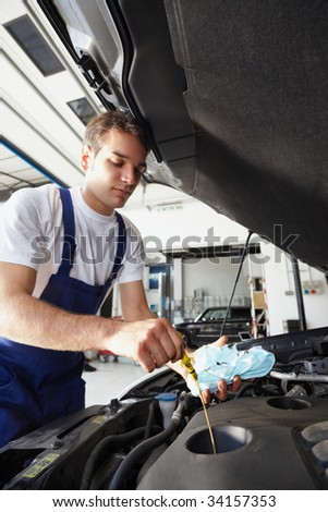side view of mechanic checking motor oil. Selective focus on hand and dipstick - stock photo