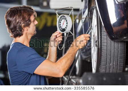 Side view of mechanic checking pressure while inflating car tire at garage - stock photo