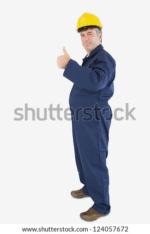 Side view of mechanic showing thumbs up sign over white background - stock photo