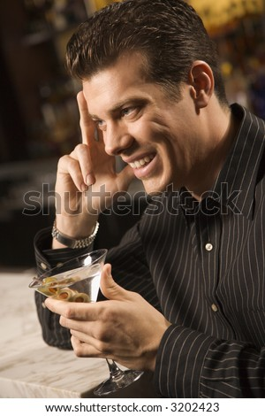 Side view of mid adult Caucasian man holding martini with hand to head smiling.