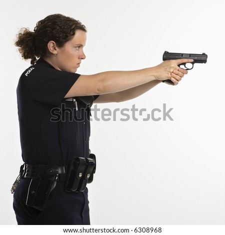 Side view of mid adult Caucasian policewoman standing and aiming handgun with arms outstretched.
