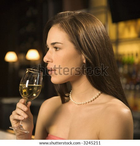 Side view of mid adult Caucasian woman sitting  at bar drinking glass of white wine.