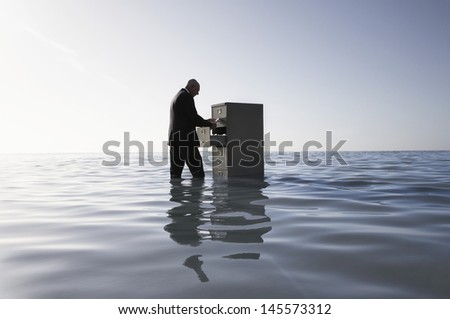 Side view of middle aged businessman opening filing cabinet in sea - stock photo