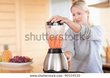 Side view of modern blender chopping fruits - stock photo