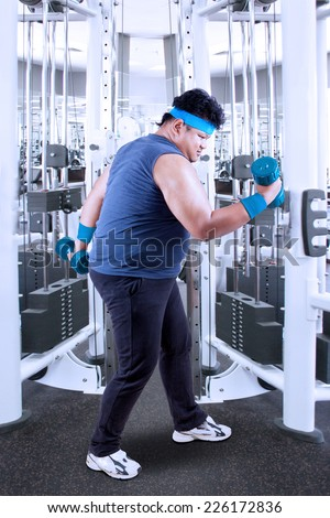 Side view of overweight person lose weight by weight lifting in the fitness center - stock photo